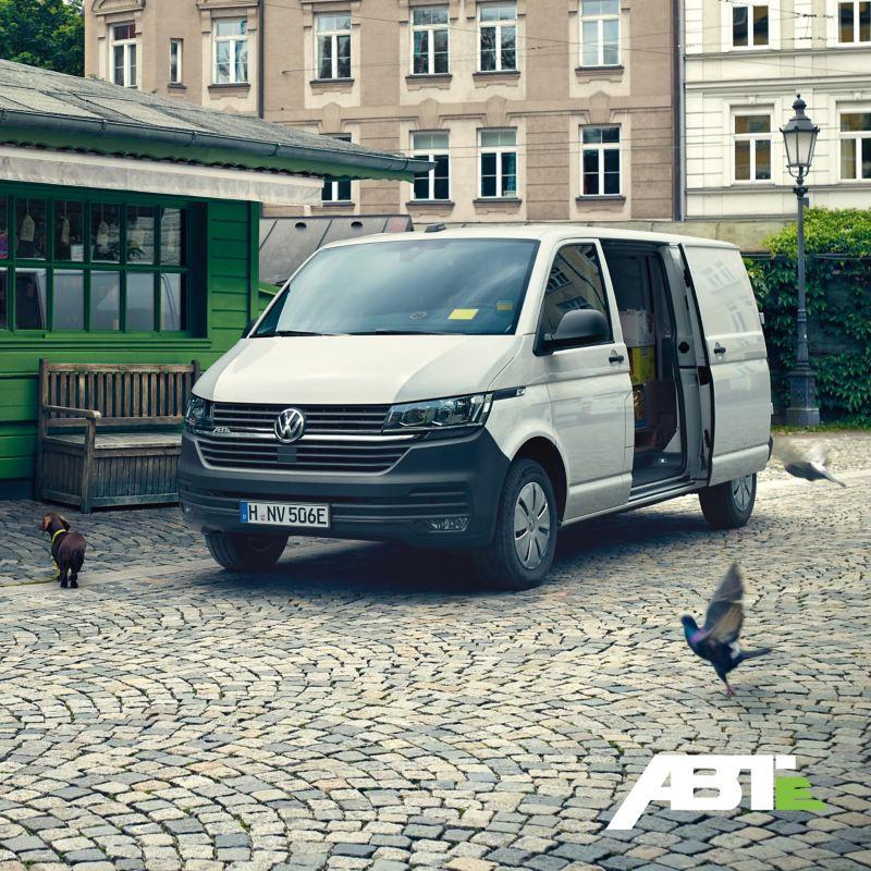 Un ABT e-Transporter avec une porte latérale ouverte se trouve devant un magasin.