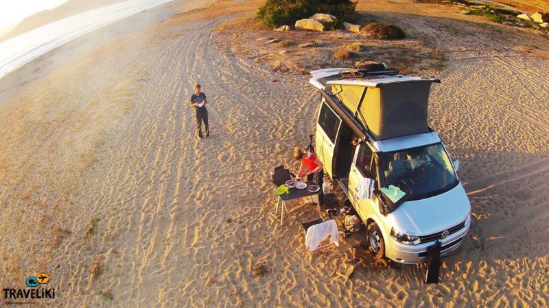 Ein Mann und eine Frau Campen am Strand mit dem VW California