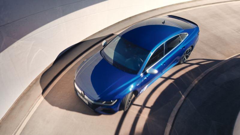 Vista desde arriba del Nuevo Volkswagen Arteon R azul bajando por una rampa