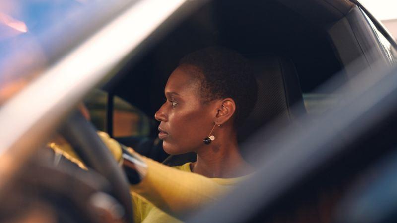 Chica al volante del Nuevo Volkswagen Arteon Shooting Brake R azul vista a través de la ventanilla