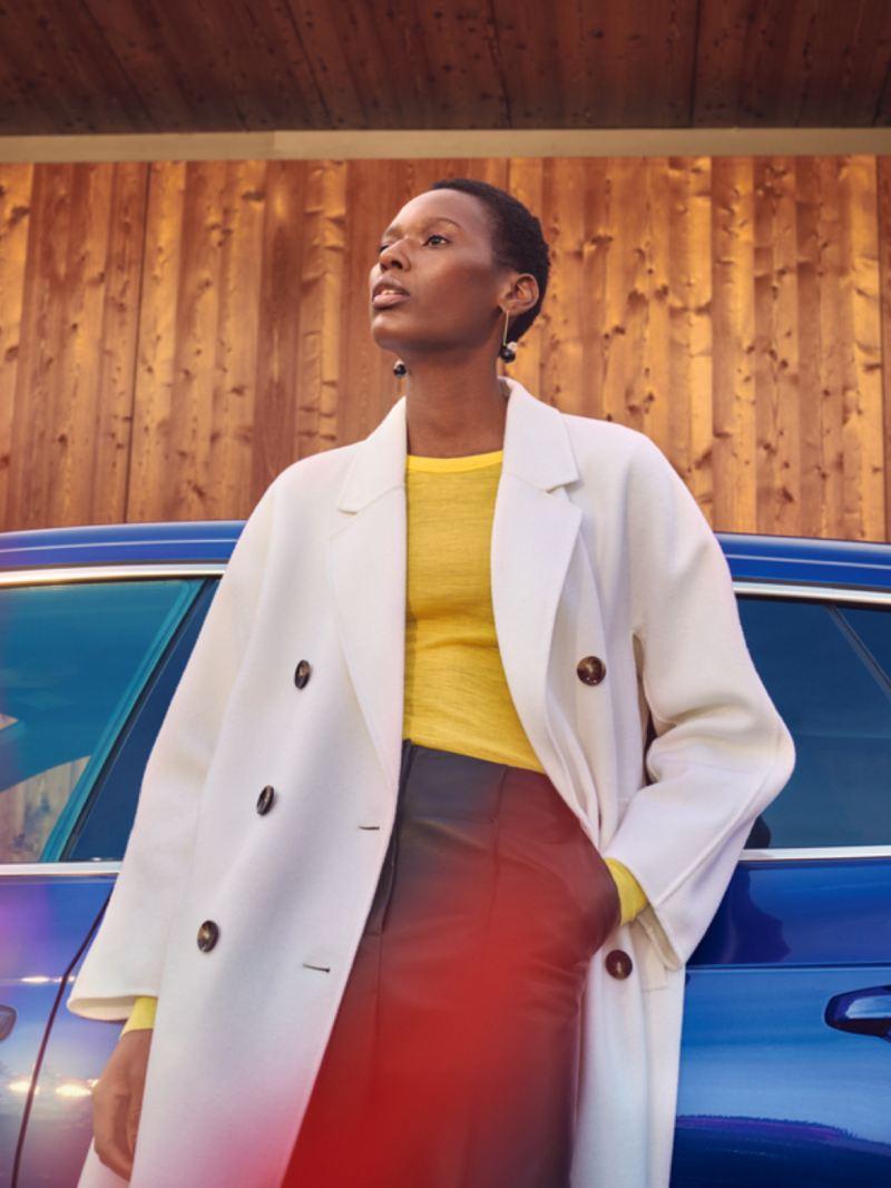 Chica con abrigo blanco apoyada en el costado del Nuevo Volkswagen Arteon Shooting Brake R