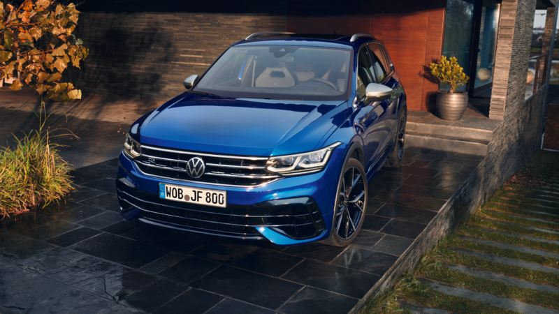 Hombre caminado delante de un Volkswagen Tiguan R azul eléctrico aparcado en una nave