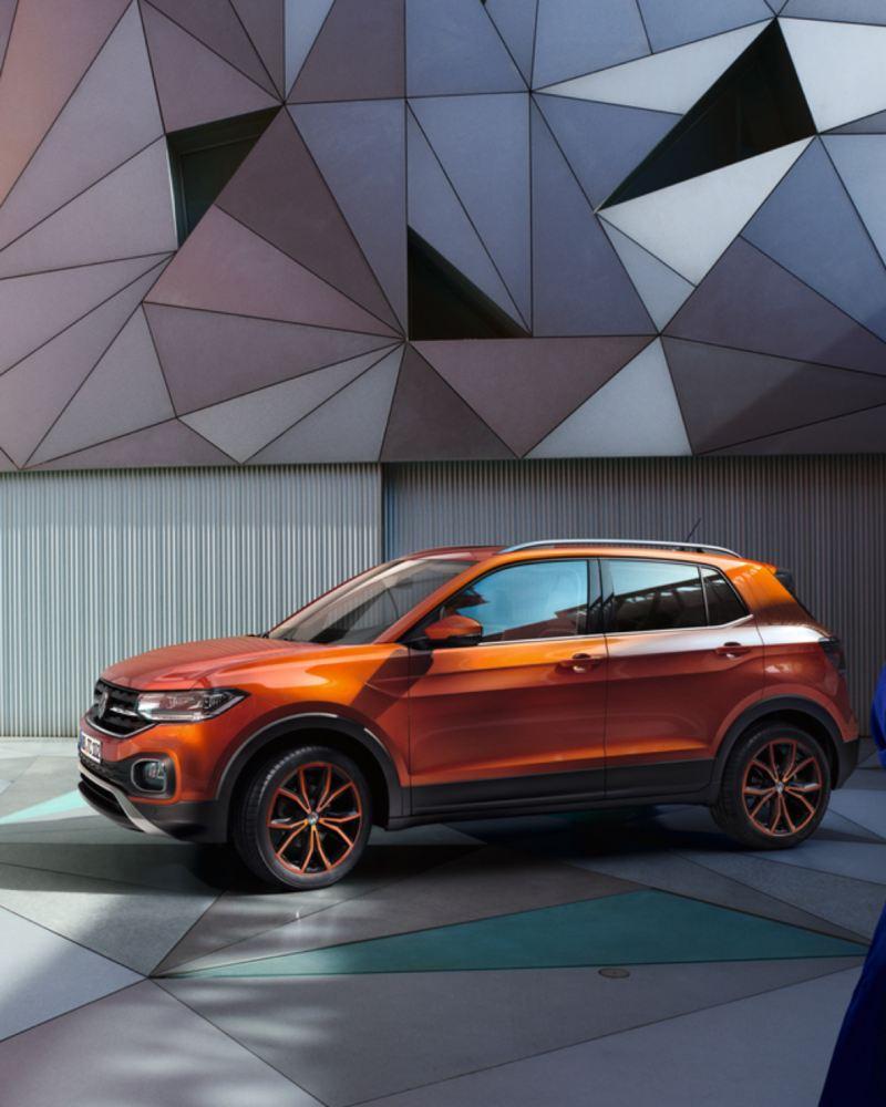 Volkswagen T-Cross naranja aparcado frente a una fachada geométrica