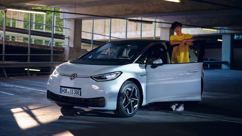 Chico de amarillo apoyado en la puerta abierta de un Volkswagen ID.3 blanco visto de frente