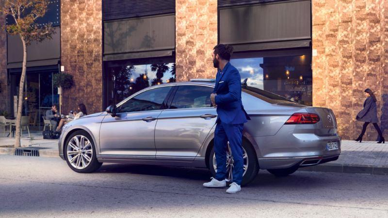 Hombre de azul de pie al costado de un Volkswagen Passat gris aparcado en la calle