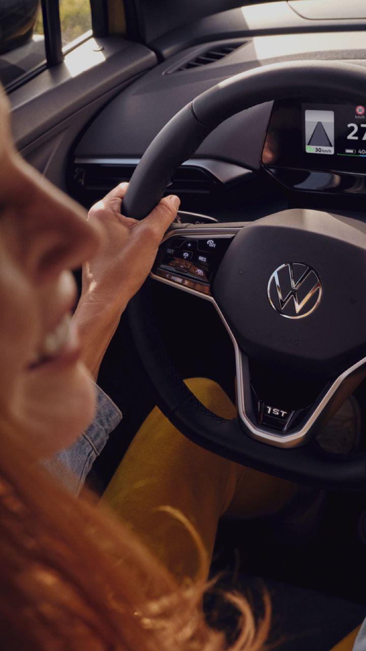 Chica en primer plano sonriendo al volante de un Volkswagen