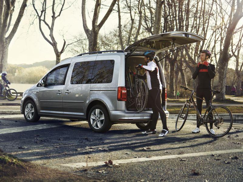 Dos hombres en un parque cargando bicicletas por el portón trasero de un Caddy