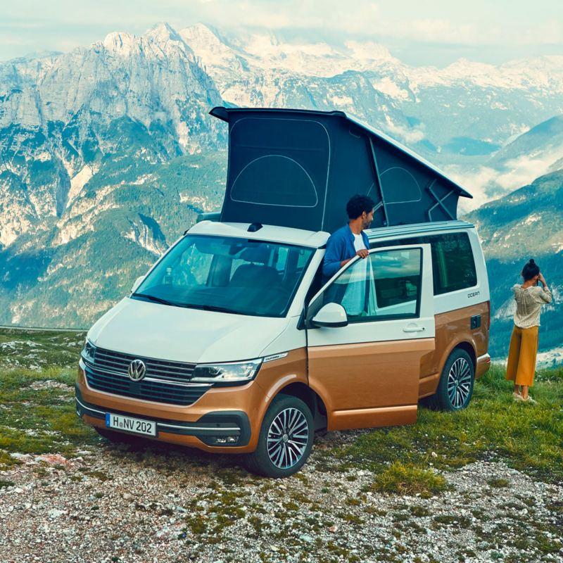 Una pareja en la montaña con un Volkswagen California con el dormitorio superior desplegado