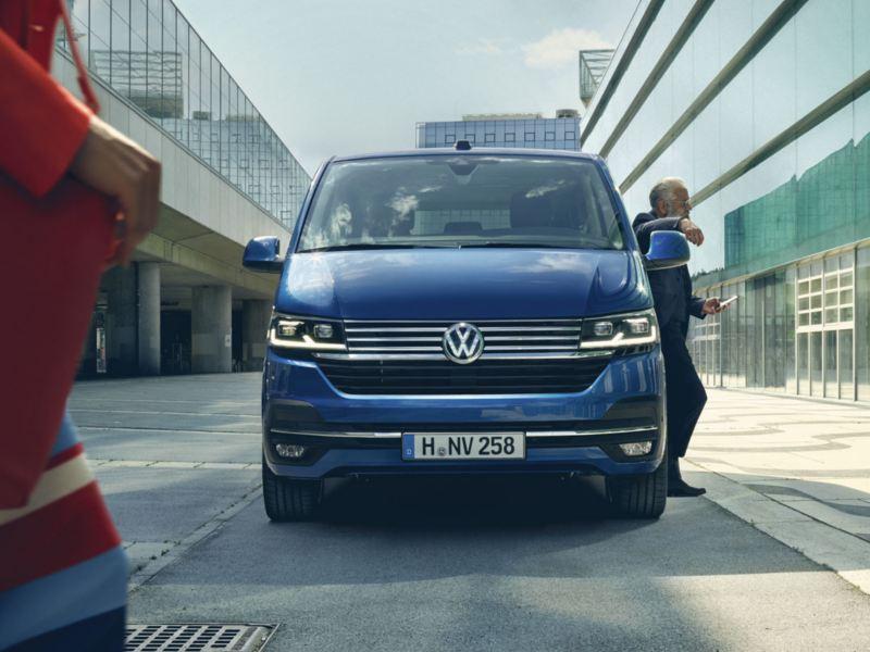 Volkswagen Caravelle azul visto de frente aparcado en la ciudad mientras baja un hombre de traje azul