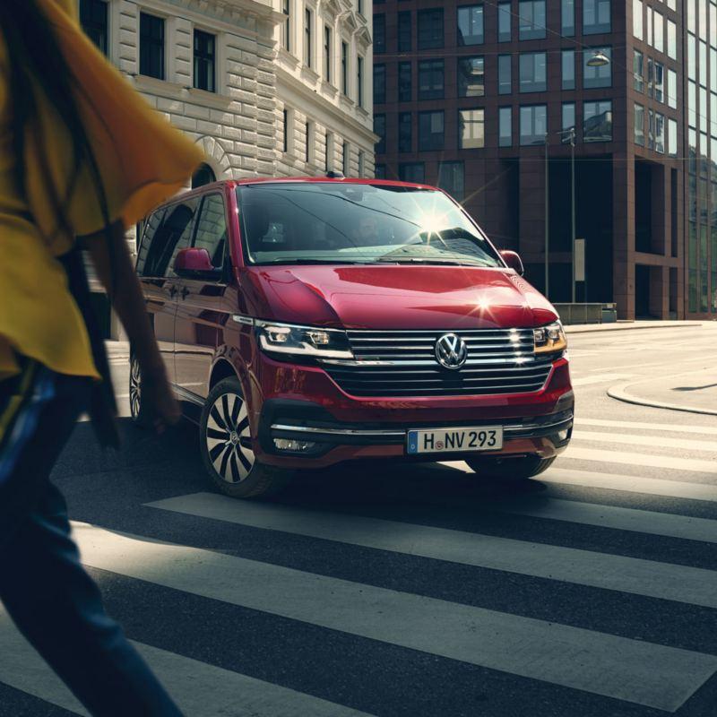 Volkswagen Multivan rojo girando en una esquina con paso de cebra que está cruzando una mujer
