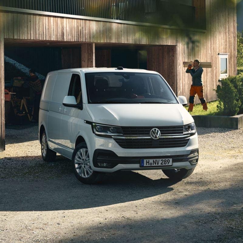 Volkswagen Transporter blanco aparcado en una casa con un hombre detrás cargando maderas