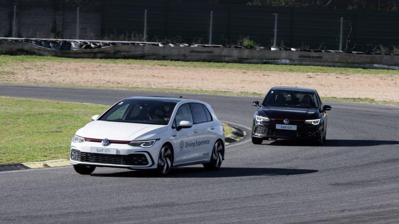 Dos Volkswagen Golf 8 vistos de frente tomando una curva en un circuito
