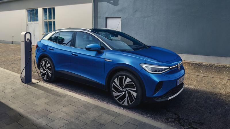 Volkswagen ID.4 azul conectado a una estación de carga en la ciudad