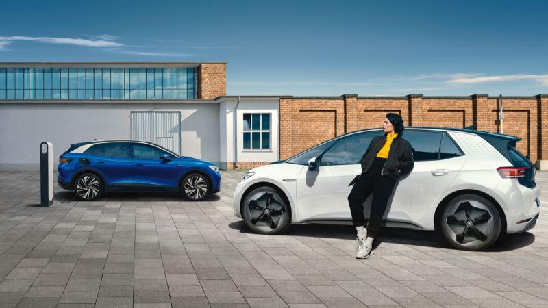 Chica apoyada en un Volkswagen un ID.3 blanco aparcado delante de un ID.4 azul vistos de costado