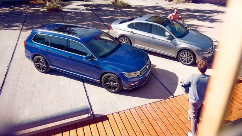 Chico saliendo de un Passat plateado junto a un Passat Variant azul aparcado en la calle