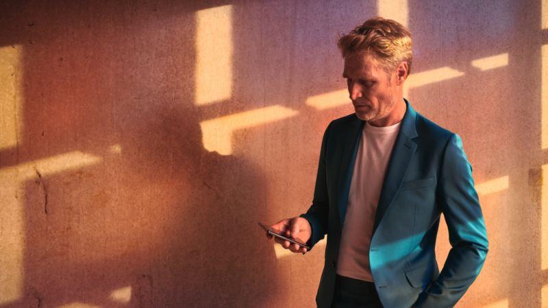 Hombre con una chaqueta azul mirando su teléfono móvil frente a una pared de madera