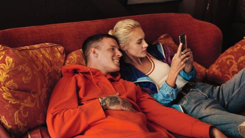 Pareja joven tumbados en un sofá mientras miran un teléfono móvil