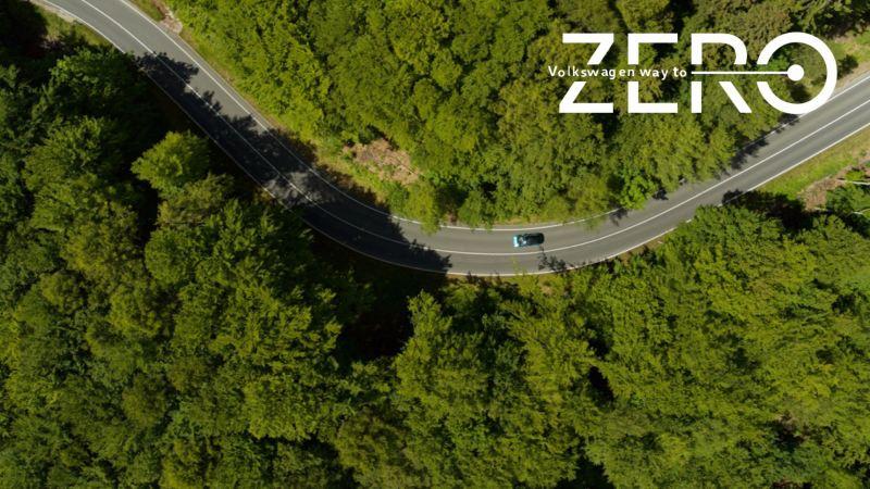 Un Volkswagen visto desde arriba circulando por una carretera en el bosque con el logo de Way to Zero sobre impreso