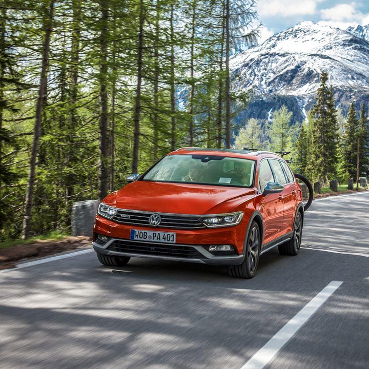 Volkswagen SUV naranja circulando en una carretera de montaña en medio del bosque con un portabicicletas