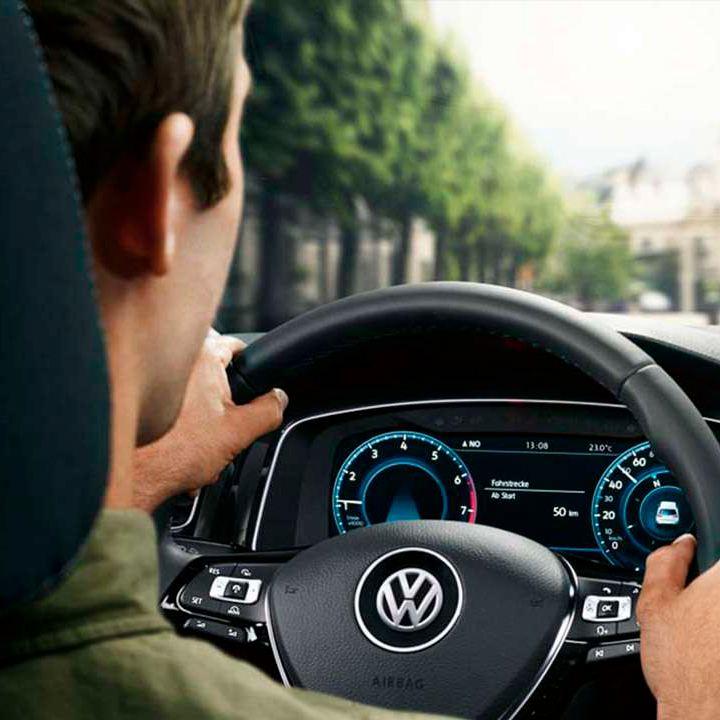 Hombre joven visto desde atrás conduciendo un Volkswagen en la ciudad