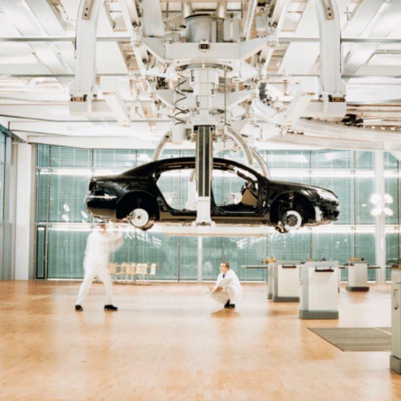 Volkswagen en una plataforma con dos operarios con mono blanco