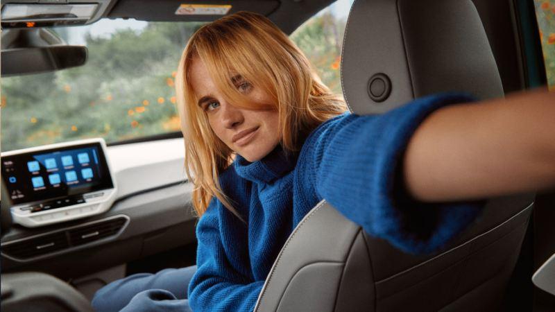 Chica sentada en el puesto del copiloto de un ID.3 vista desde el asiento de atrás