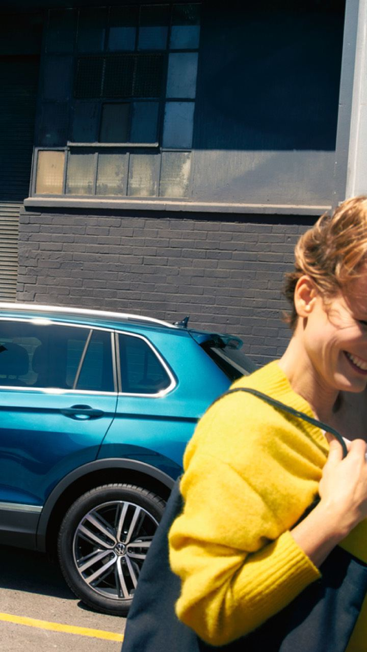 Mujer de amarillo sonriendo delante de un Volkswagen azul aparcado en la calle