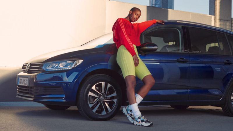 Chica joven vestida de rojo y verde apoyada en el costado de un Volkswagen azul