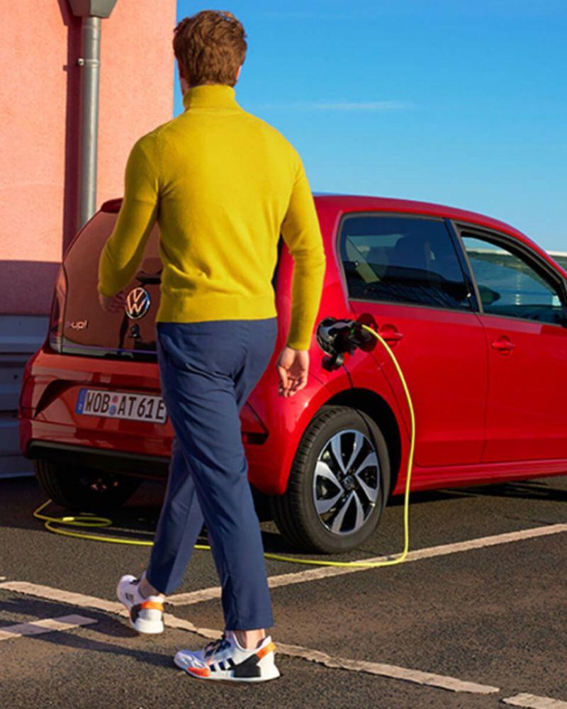 Chico con jersey amarillo caminando hacia un Volkswagen e-Up! rojo conectado a un cargador elécrico