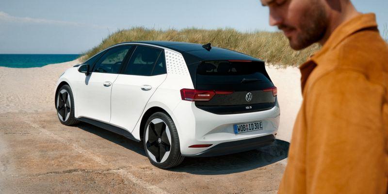 Volkswagen ID.3 blanco aparcado frente a una playa con un chico en primer plano