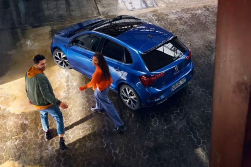 Un chico  y una chica caminando hacia un Volkswagen Polo azul vistos desde arriba