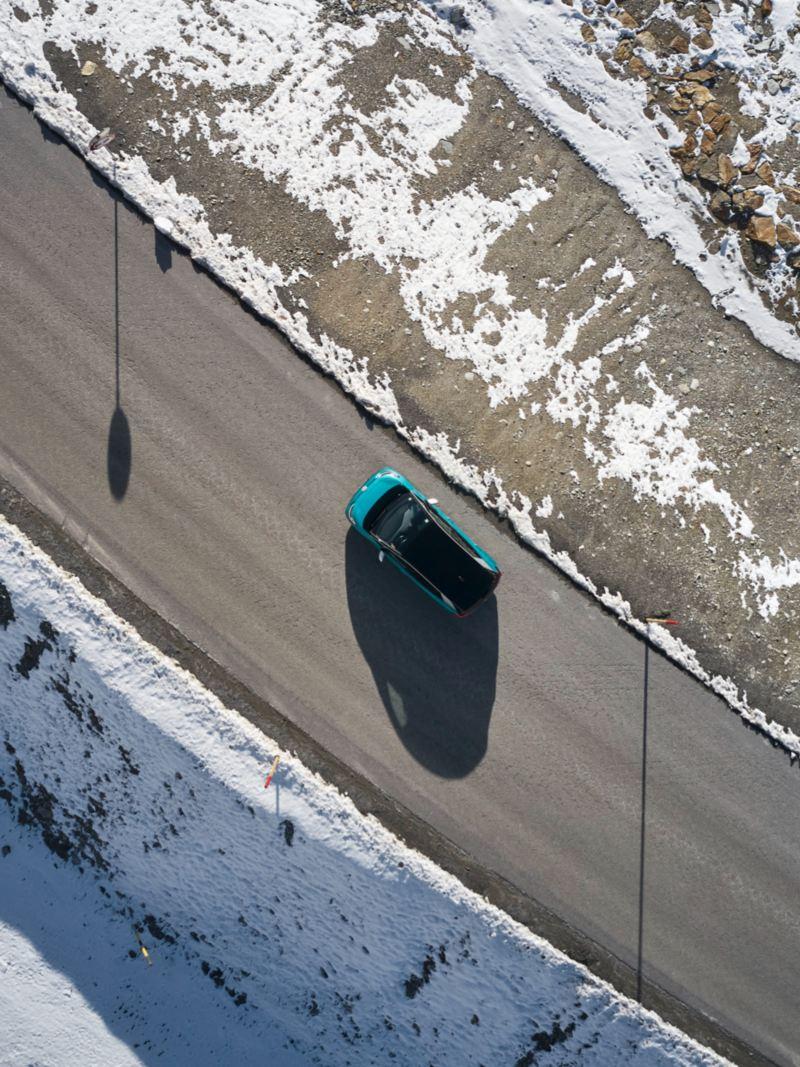 Volkswagen ID.3 verde visto de frente circulando por una carretera en el bosque