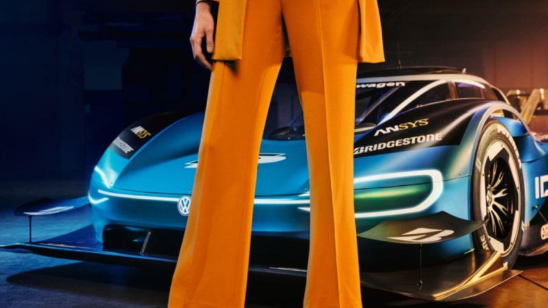 Primer plano de las piernas de una chica con pantalones naranja delante de un ID. R aparcado
