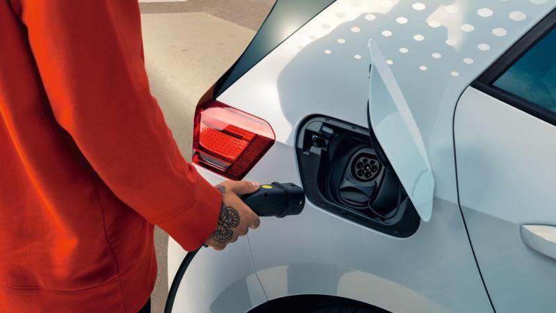 Detalle de la mano de una persona conectando el cargador eléctrico a un Volkswagen