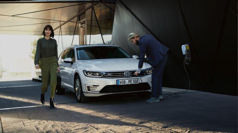 Hombre conectado el cargador eléctrico a un Volkswagen Passat GTE blanco mientras una chica camina delante