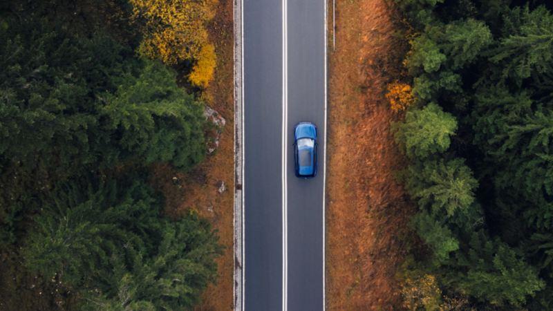 Vista aerea de un SUV de Volkswagen en una carretera en el bosque