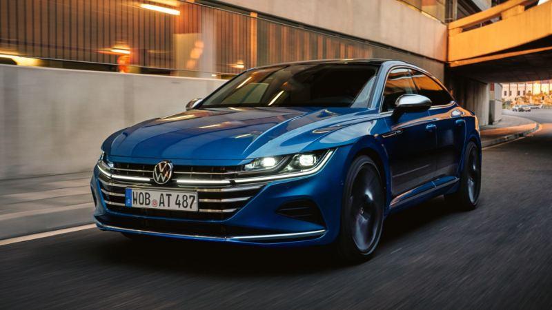 Vista frontal de un Nuevo Volkswagen Arteon azul avanzando por la carretera