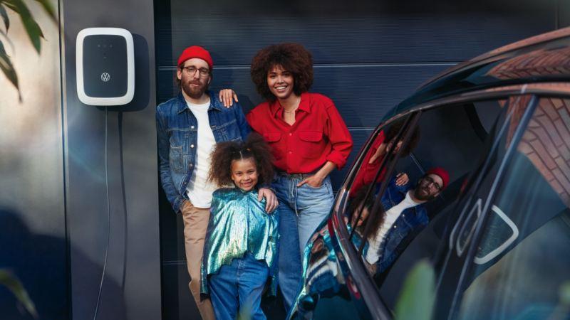 Una familia junto a un cargador eléctrico en el parking de casa