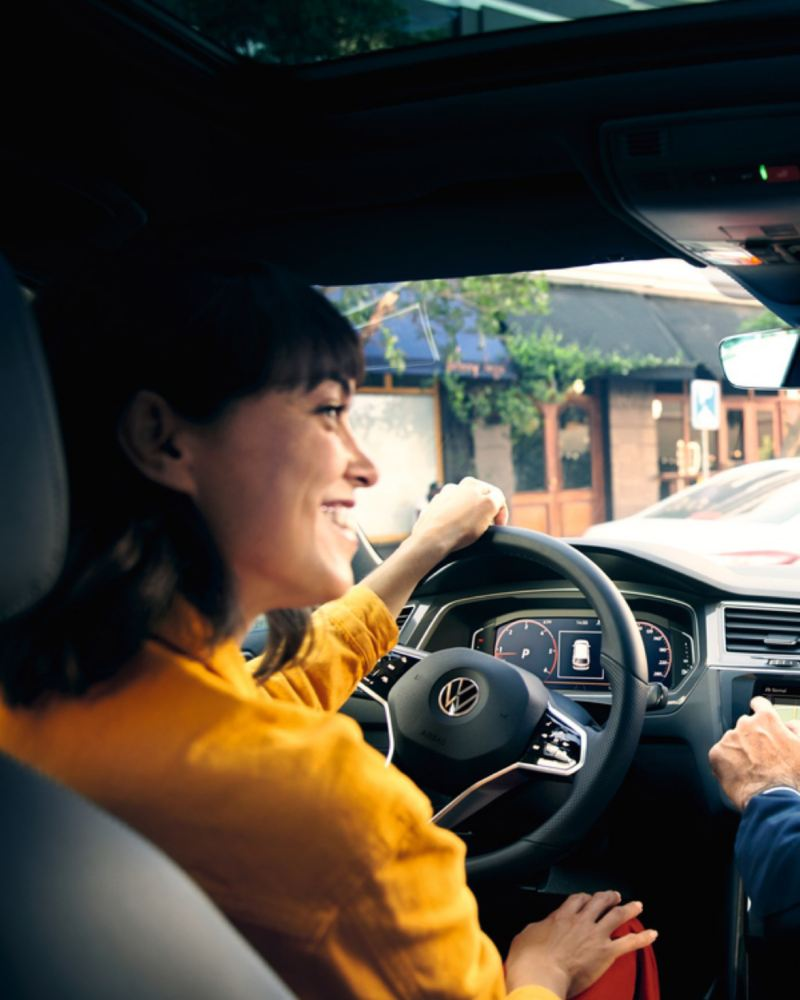 Mujer sonriendo al volante de un Volkswagen vista desde atrás