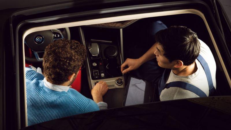 Un chico con un agente de servicio dentro de un Volkswagen vistos de arriba a través del techo solar