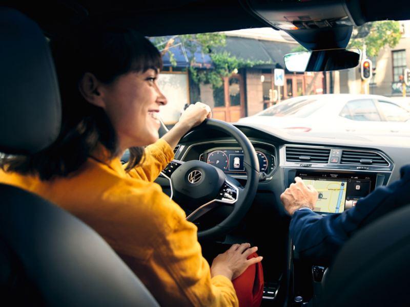 Chica de amarillo al volante de un Volkswagen vista desde el asiento trasero
