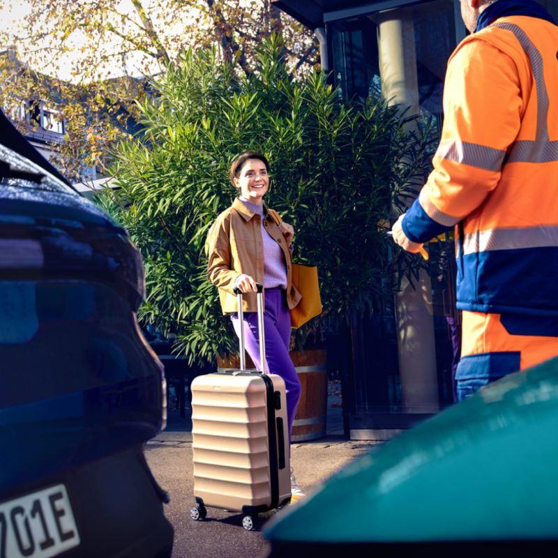 Mujer de pie con una maleta mirando a un agente de servicio Volkswagen en primer plano
