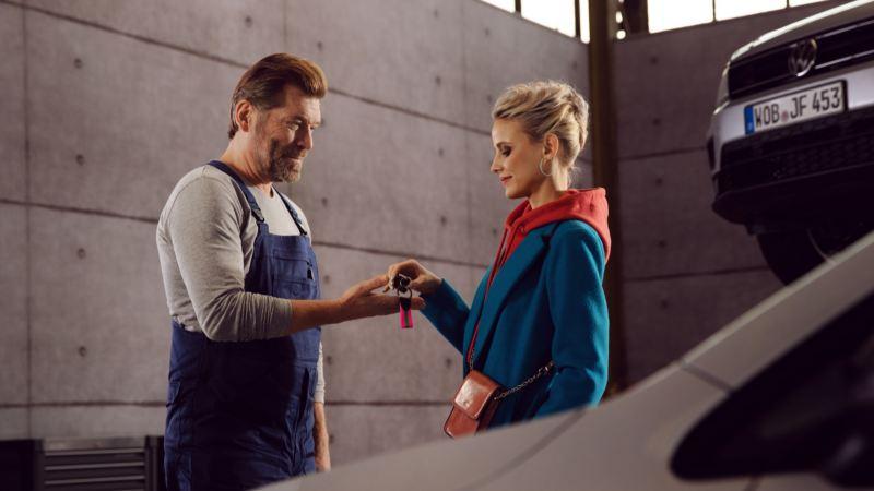 Una mujer entregando las llaves de su Volkswagen a un mecánico en el taller