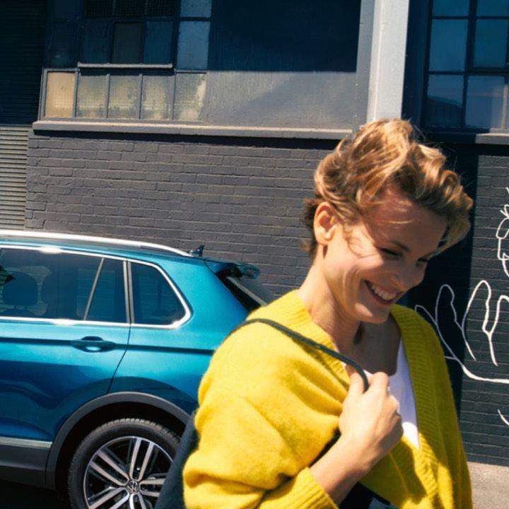 Chica sonriendo delante de un Volkswagen aparcado en la calle