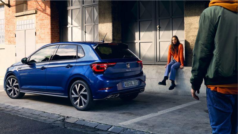 Volkswagen Polo azul aparcado junto a una nave industrial y una chica sentada en un escalón