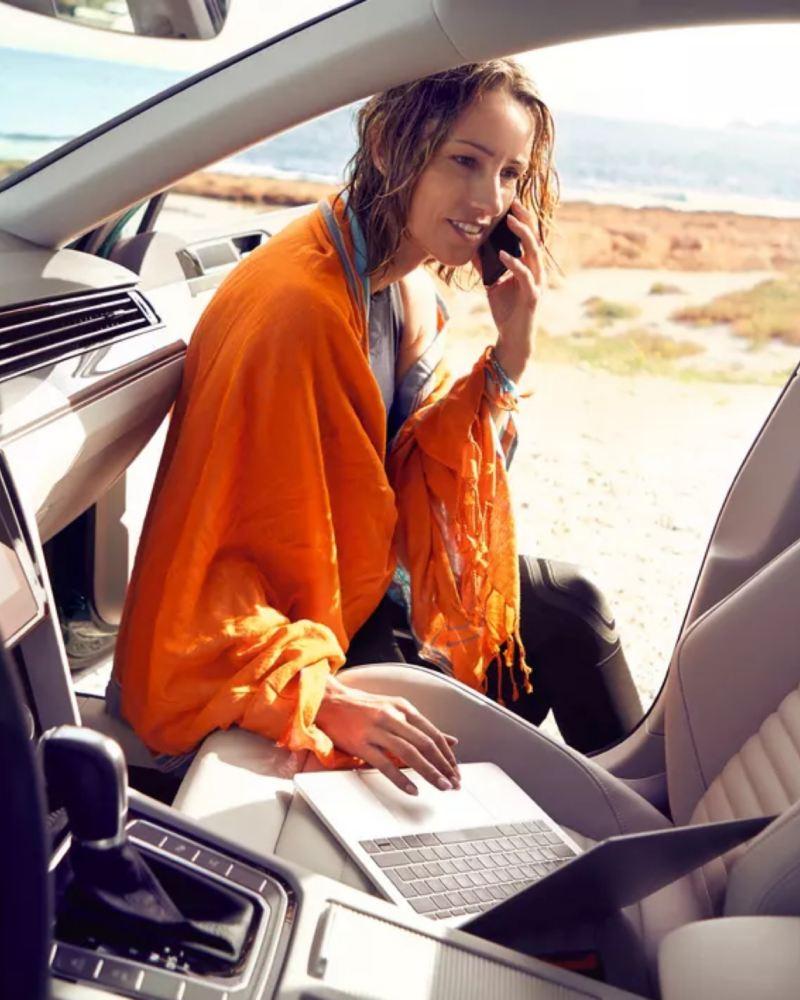 Chica en la playa hablando por teléfono y un portátil apoyado en el asiento delantero de un Volkswagen