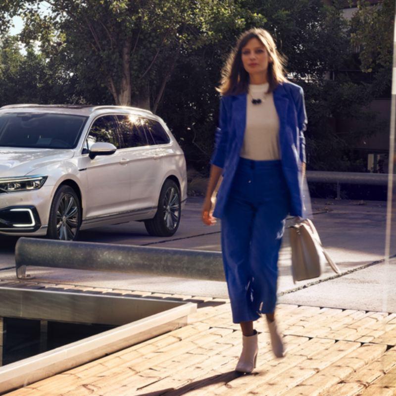 Mujer vestida de azul caminado y un Volkswagen Passat que se ve parcialmente al costado