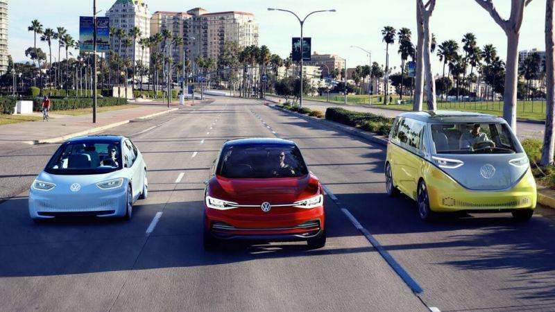 Gama de coches eléctricos de Volkswagen vistos de frente circulando por un calle en la ciudad