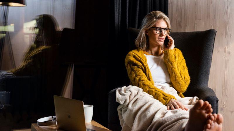 Chica con jersey amarillo tumbada en un sofá hablando por teléfono
