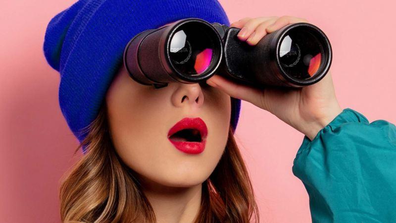 Imagen de chica con binoculares apuntando su mirada hacia el sur.